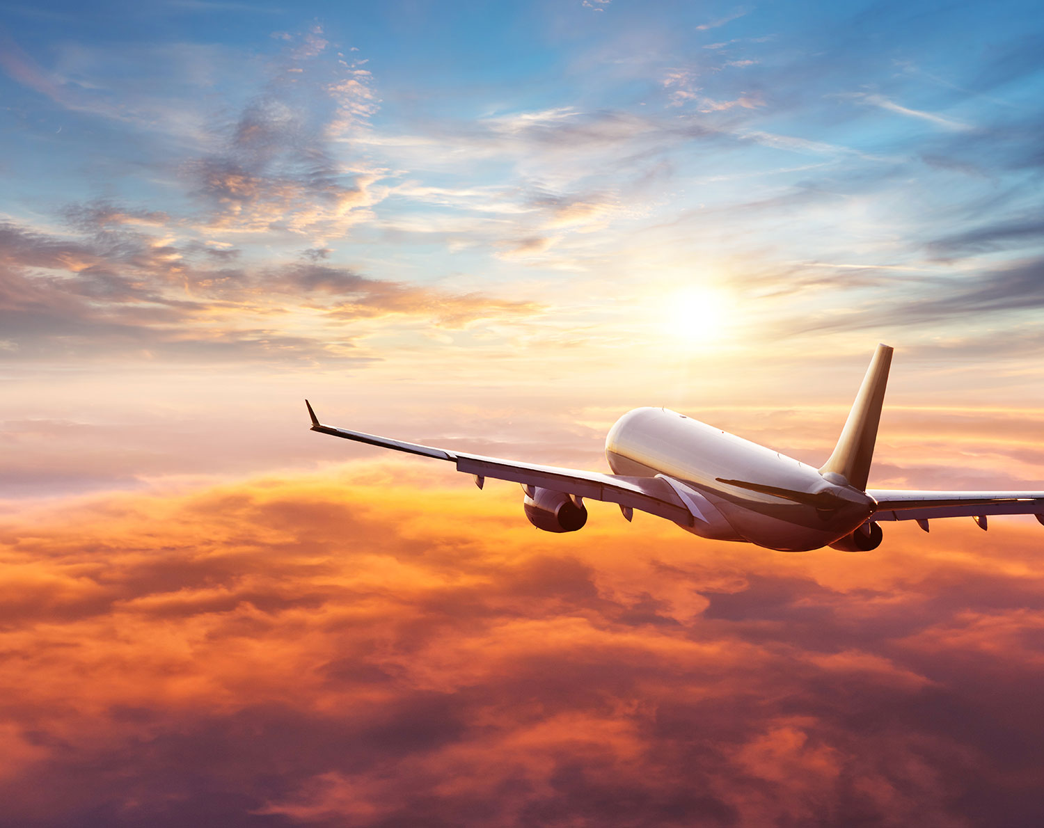 Aeroplane flying above the clouds in a sunset – global payroll services. Our international payroll services and FX payment products provide businesses with a convenient way to pay their staff and suppliers worldwide.