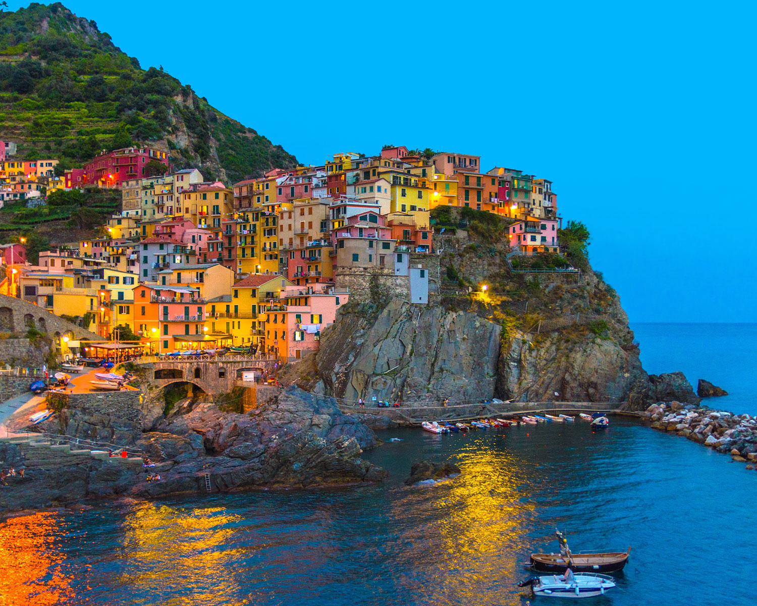 Manarola traditional typical Italian village in National park Cinque Terre with colourful multi-coloured buildings houses on rock cliff and marine harbour, night evening view – international payments for buying or selling a property abroad. RationalFX can help you save money on your overseas transfers when you make a payment purchasing home abroad.