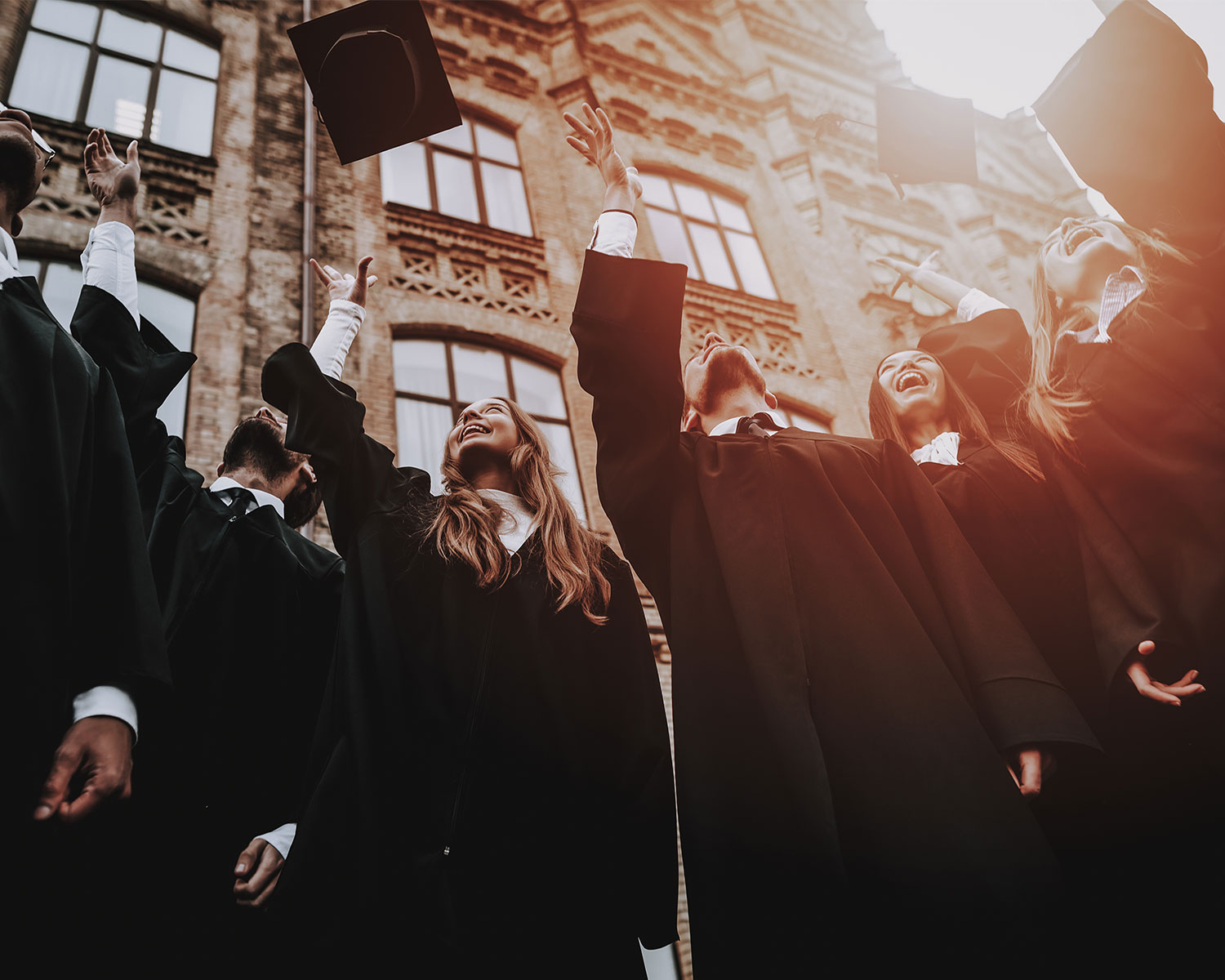 Students throwing graduation caps in the air outside building – paying overseas tuition fees. Our international payment services help you to save money when making payments for studying abroad and overseas education.