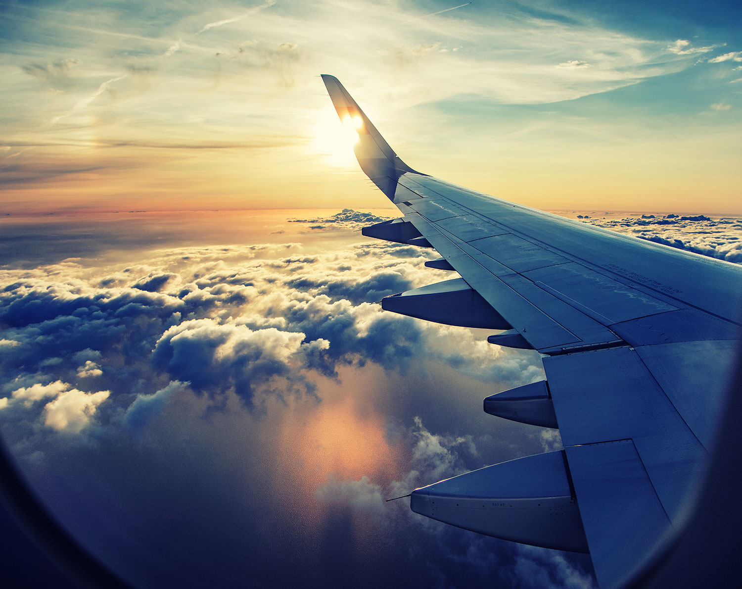 Aeroplane flying above the clouds – money transfers for moving abroad. International payments for moving overseas and emigrating, including regular overseas payments.