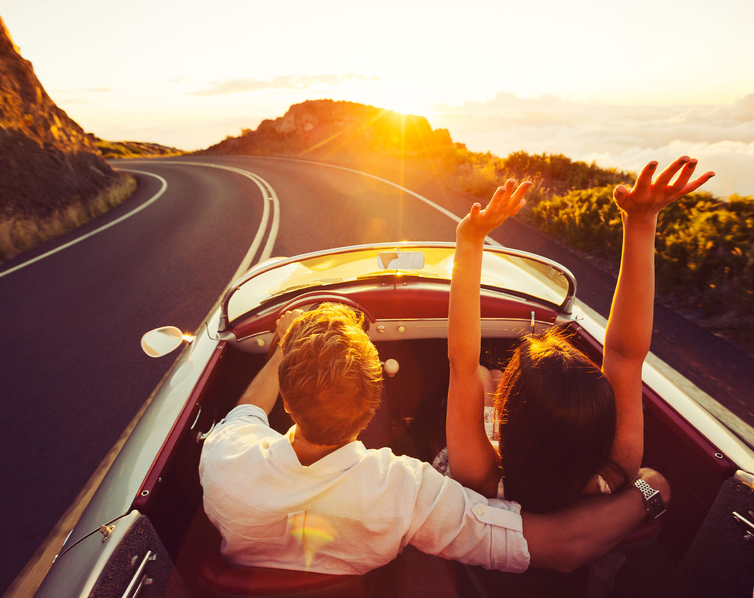 Couple driving along a mountain road in an open top car with sun gleam – importing luxury goods from abroad. Save money on international payments when buying a yacht from abroad, buying a car from abroad or importing a luxury good from abroad.