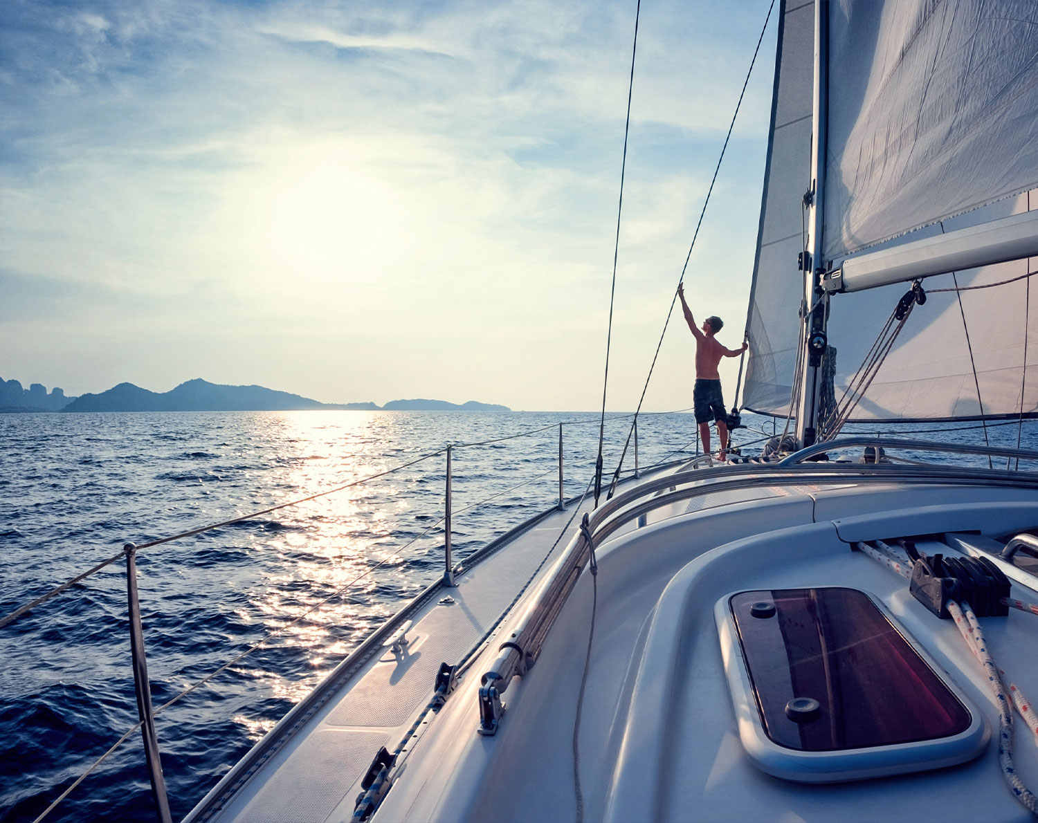 Person sailing on a boat – cross border payments for personal clients. RationalFX help individual clients to save time and money when making money transfers abroad.