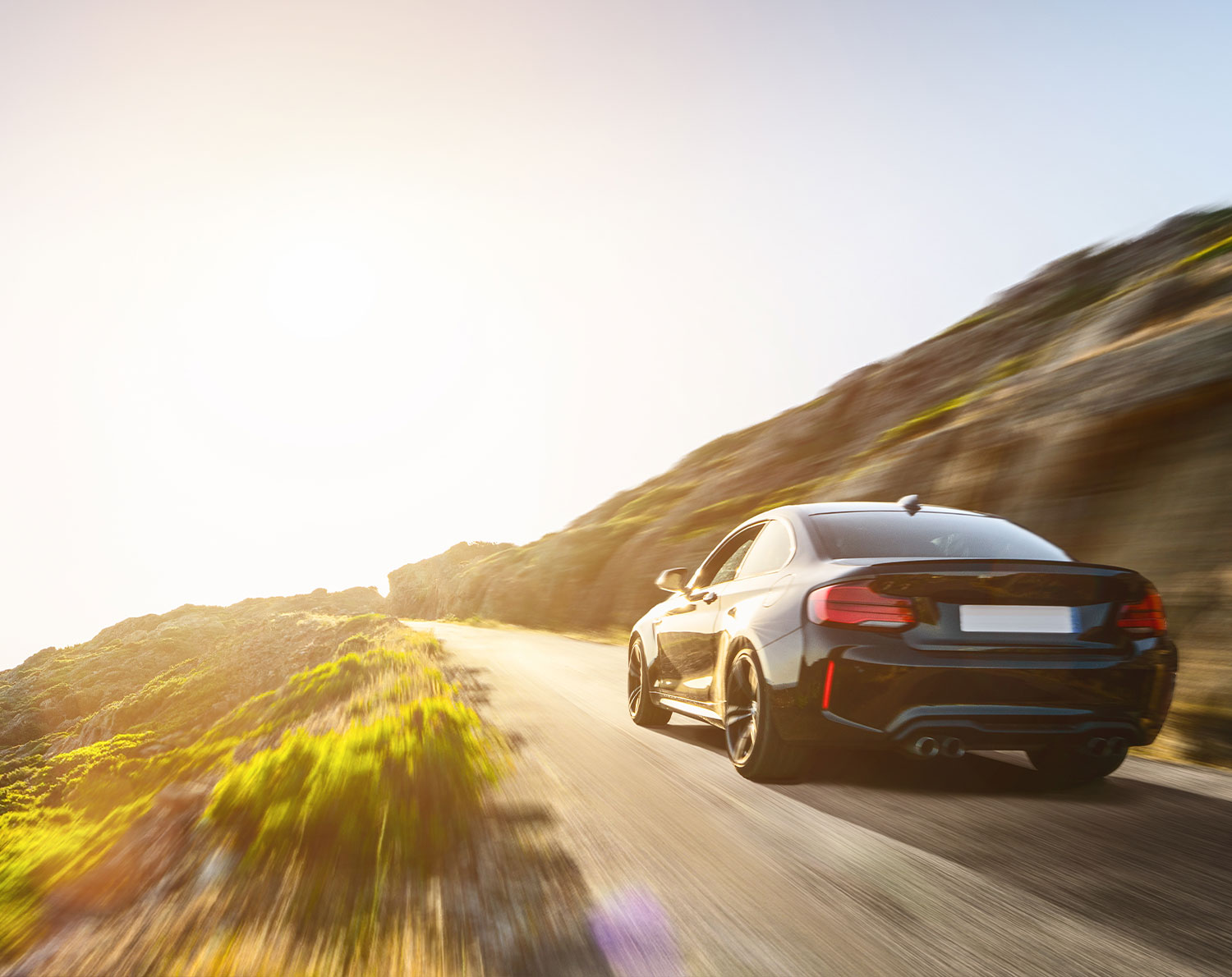 Black car driving on a mountain road – how RationalFX can help. International money transfers with competitive exchange rates and low to no transfer fees and expert guidance.