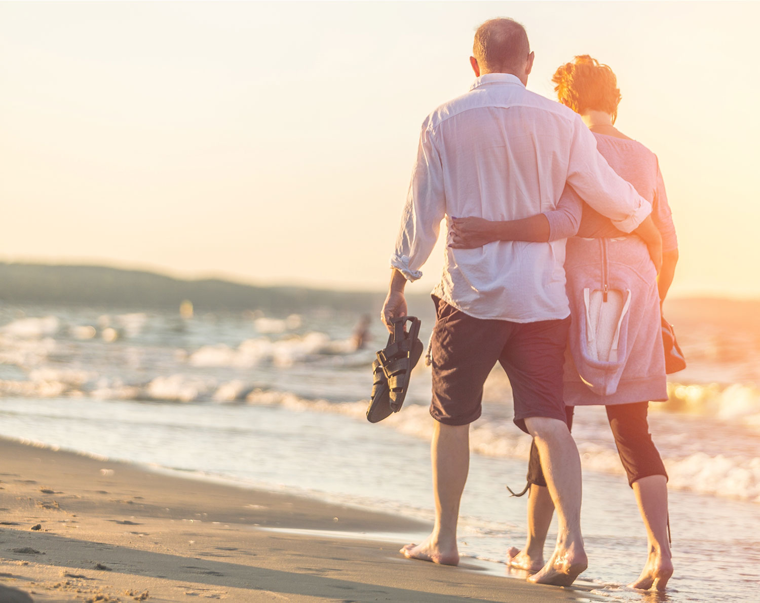 Close-up portrait of elderly couple hugging on seafront – moving pension payments abroad. RationalFX can help you transfer uk pension payments abroad. Move your UK pension living abroad or plan your pension when moving abroad.