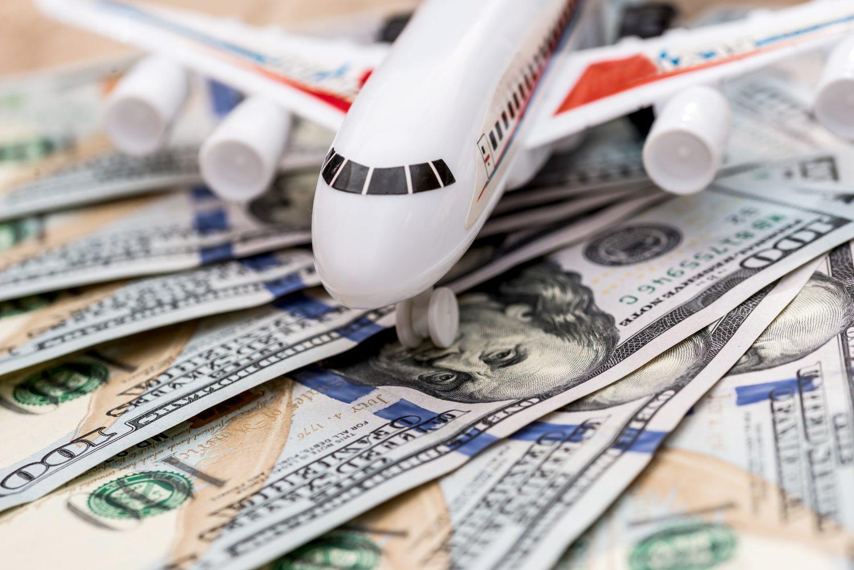 buy travel money online - airplane on dollar bills close up